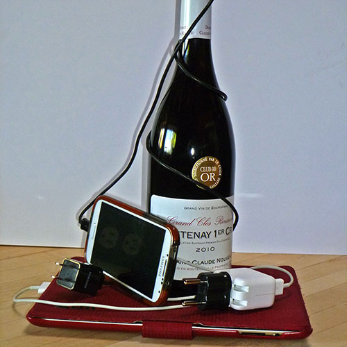 A French wine bottle with mobile phone, tablet and electrical cords.