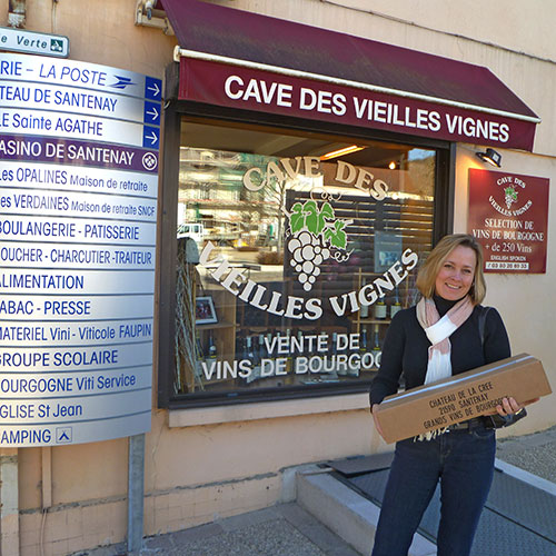 Lady holding package in front of wine store in Burgundy France